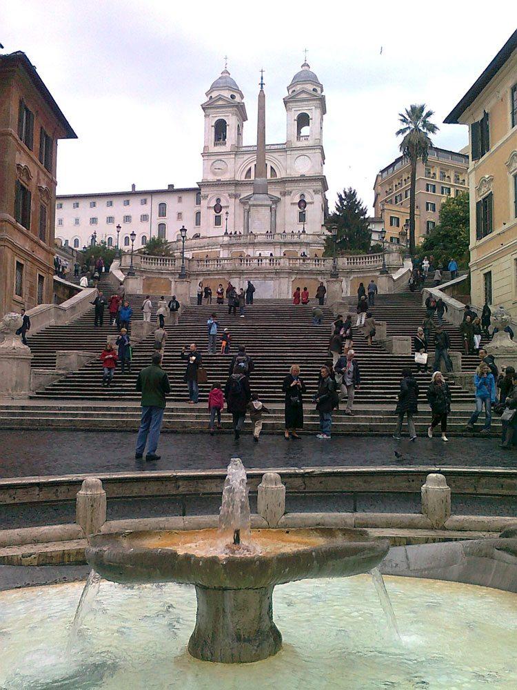 """""""Spansketrappen"""" har fått navnet etter Spanskeplassen som ligger like bortenfor trappen. Der ligger også den spanske ambassaden. Men trappen skulle egentlig hatt navnet """"Fransketrappen"""", for det var den franske diplomaten Gueffier som bekostet byggingen av trappen. Byggingen begynte i 1723 og sto ferdig 3 år senere På toppen av trappen ligger også en fransk kirke som heter Trinita Dei Monti. Kirken ble grunnlagt i 1495. 21. april bli trappen pyntet med blomster, da har Roma geburtsdag. Det sier i alle fall legenden, og det er en historie for seg. (Foto: Britt Hilt Caspersen)"""