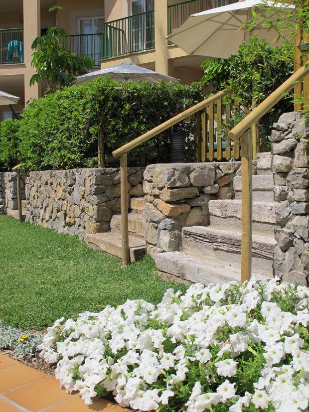 Her fins mye å bli inspirert av. Et parti fra Viva Cala Mesquida Resort (Mallorca) med et vell av petunia ved siden av en tretrapp laget av sviller. Se også de praktfulle murene, plenen, hekken, terrassene. Veldig pent utført. (Foto: John Steffensen)