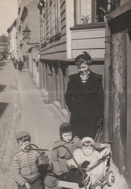 I den stilige barnevognen sitter jeg, John. Nærmest meg min bror, Gunnar. Det tredje barnet er Ole Bjørn, men ham husker ikke jeg. Sammen med mammaen min venter vi på Frank på motsatt side av gaten der Frank sitt første skomakerverksted (i nummer 17).